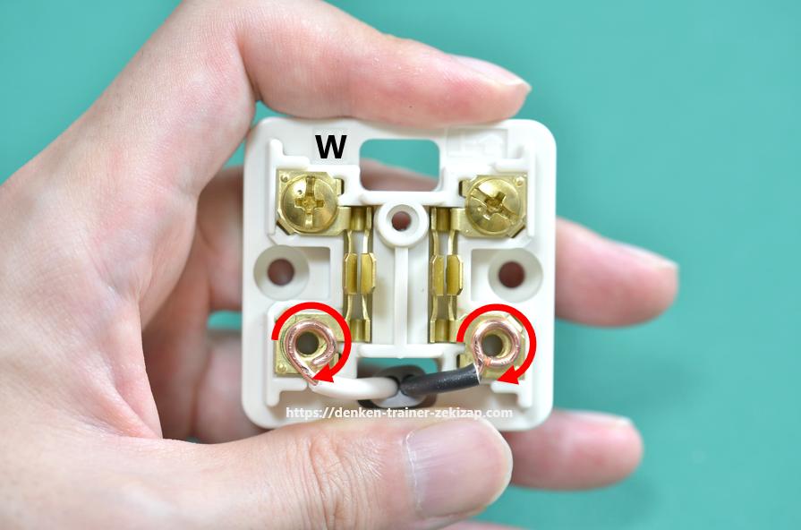 露出形コンセントの接地側端子に白色電線を結線して、輪作りが右巻きになっていることを説明する画像