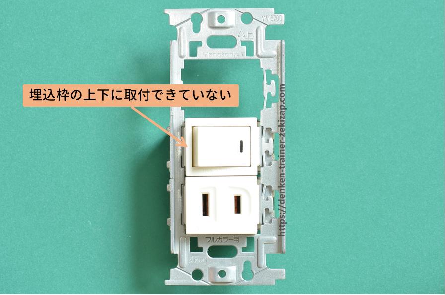 埋込連用取付枠にコンセントと片切スイッチを上下に取り付けた欠陥画像2