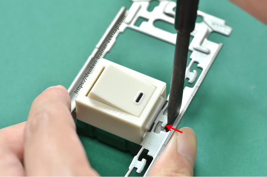 埋込連用取付枠に片切スイッチを取り付けるためにマイナスドライバーを金具穴に押し込む画像